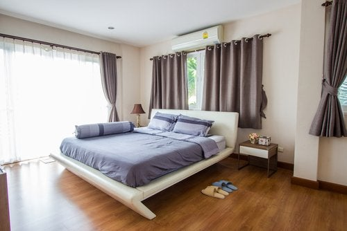 Blue bedding hardwood floors neutral walls and curtains relaxing bedroom