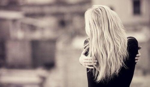Woman hugging herself self love black white self-pity