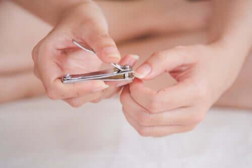 A woman cutting her fingernails.