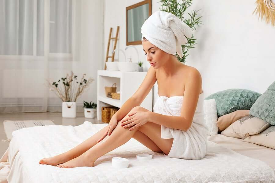 A woman massaging her legs with lotion.