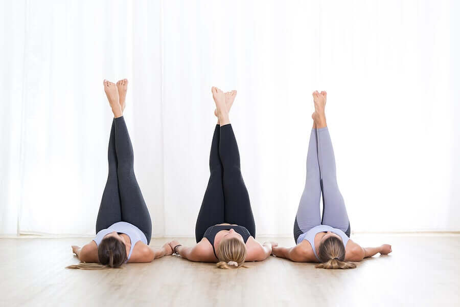 Three women exercising with their legs in the air.