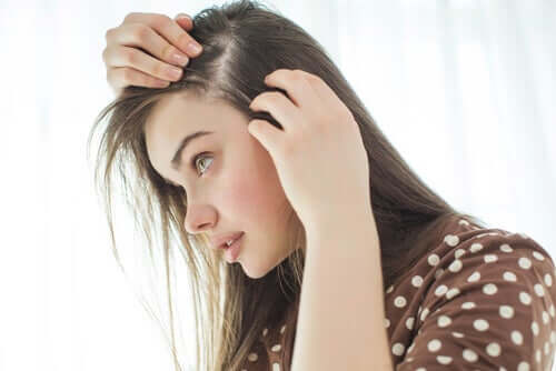A young woman looking for grey hairs.