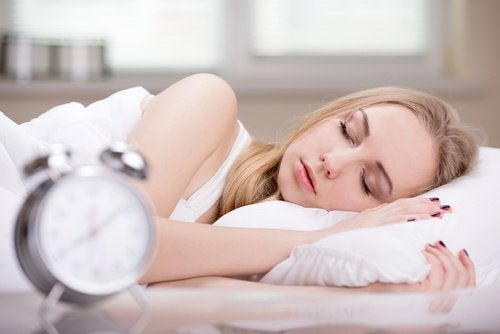Woman asleep with alarm clock