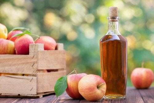 A box of apples and a bottle of vinegar.
