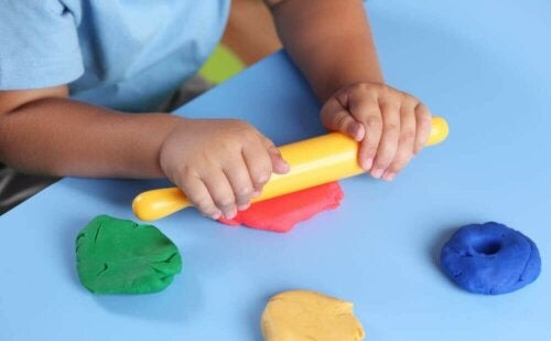 A child rolling out some plasticine.