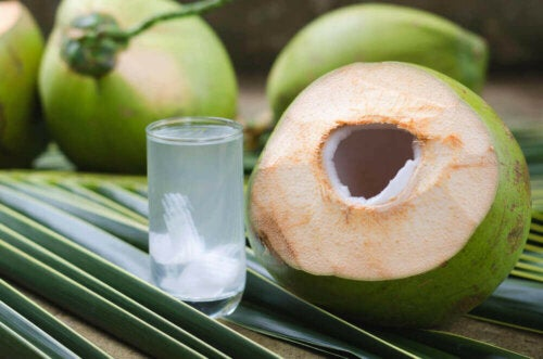 A glass of coconut water next to a coconut.