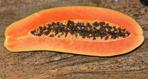 A papaya on a stone table.