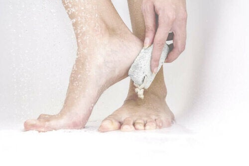 A person rubbing their cracked heels with a pumice stone.