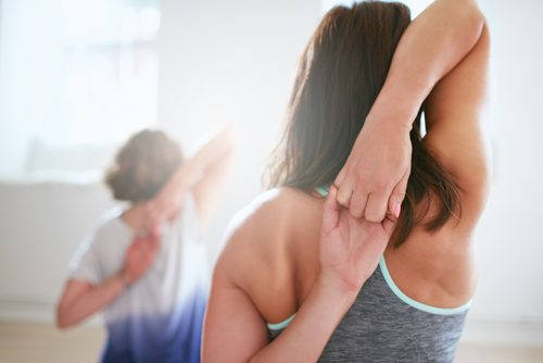 A woman stretching to relieve shoulder pain.