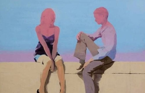 A couple talking sitting on a wall