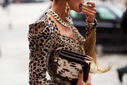 Woman in street eating something and wearing necklace, animal print jacket and carrying animal print purse fashion mistakes