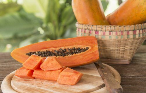 Papaya on wooden cutting board remove seeds for kiwi smoothies