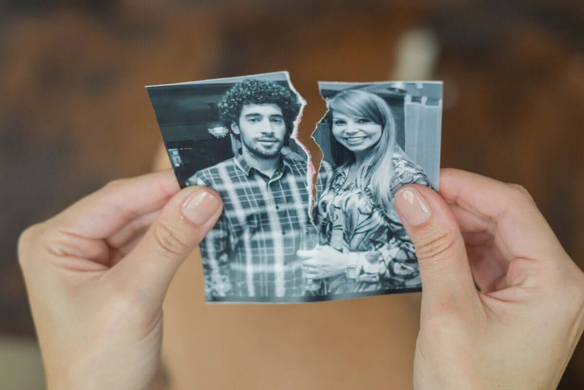 A woman ripping a photo of her and her ex.