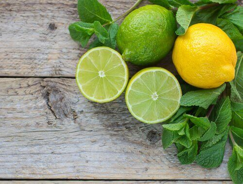 Lemon and lime halves with mint leaves on a wooden surface uses for lemons