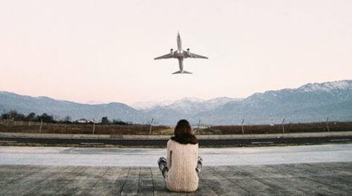 person watching a plane depart and contemplating life