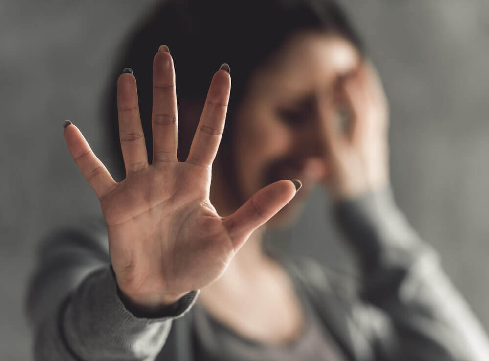 A woman crying and holding her hand out in front of her.