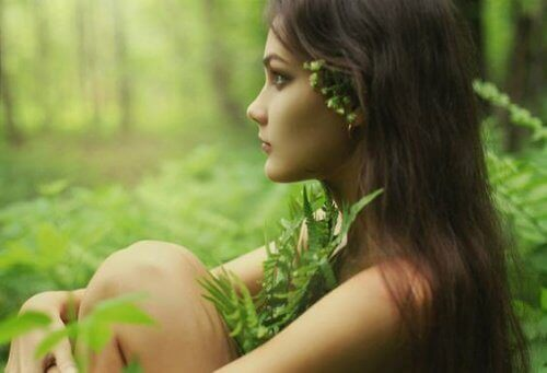 Faerie woman with plants as clothes sits in forest contemplating fight mental exhaustion