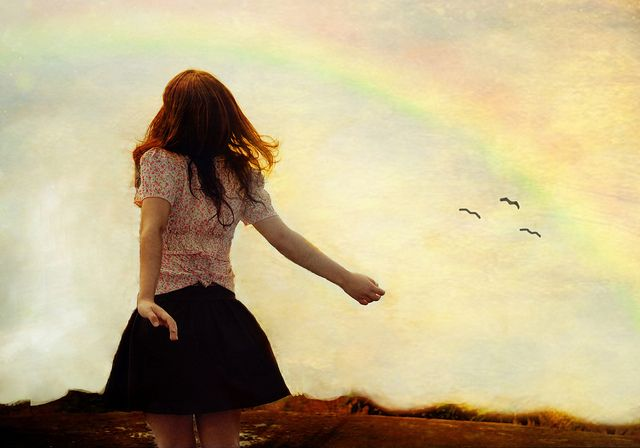 A woman looking at a rainbow.