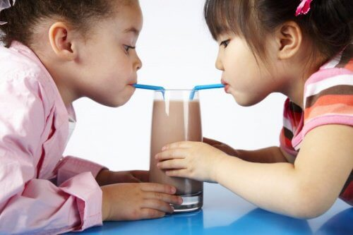 Two little girls sharing a chocolate shake