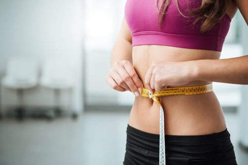 A slim woman measuring her stomach.