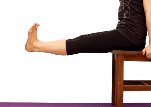 A woman sitting on a chair doing exercises