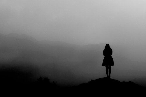 Woman on a peak overlooking view foggy black and white cold accept your present situation