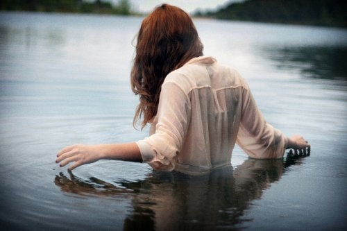 Woman dressed in a white button down shirt wading in a lake accept your present situation