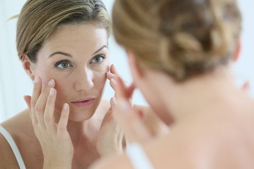 woman looking in mirror at her clear face