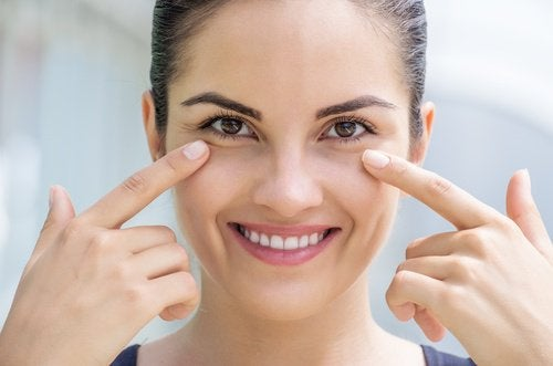 woman pointing to her face to show healthy skin