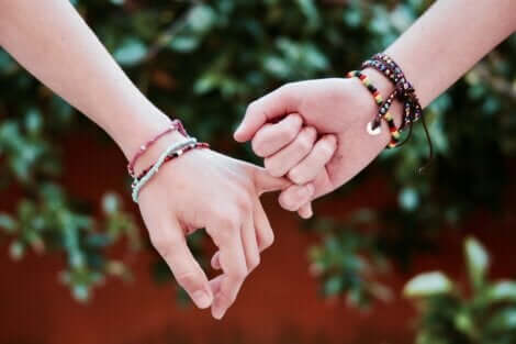 A teen couple holding hands.