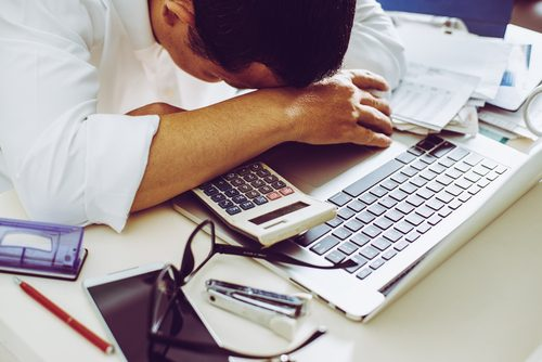 Man sleeps on his desk at work doing math finances depression and cancer