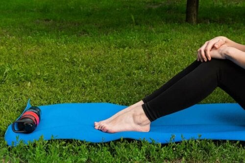 A person sitting on a yoga mat.