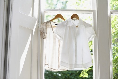 Two shirts haging indoors to dry