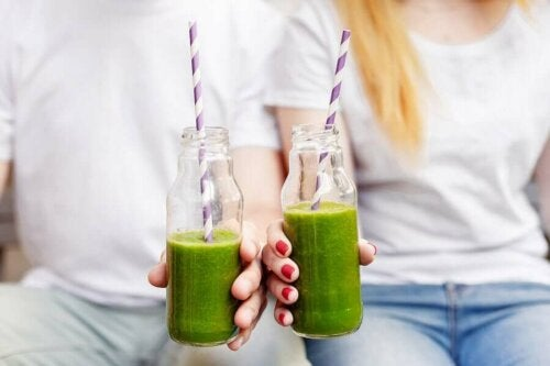 Two people drinking green shakes.