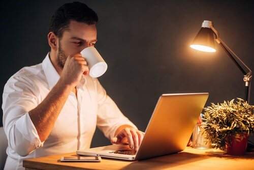A man working on his computer late at night and drinking coffee