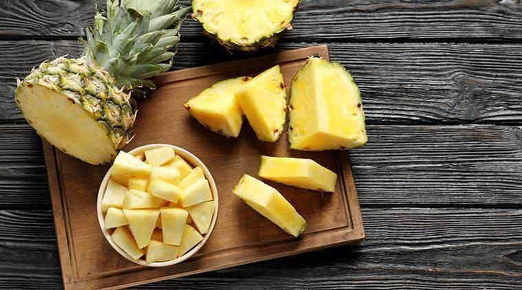 A cutting board and pineapple chunks.