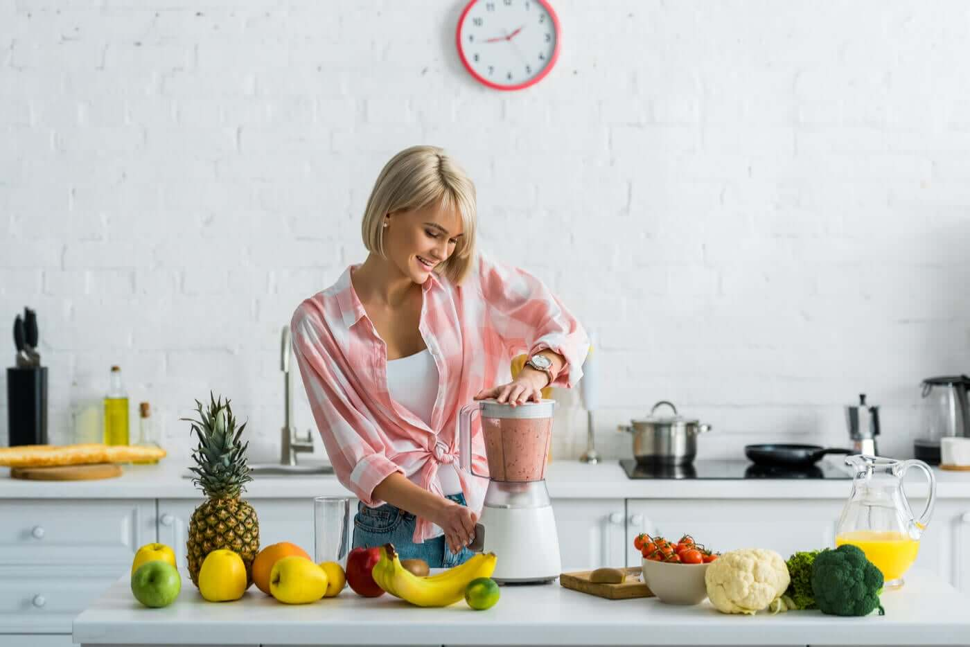 A woman preparing fruit smoothies in her kitchen.