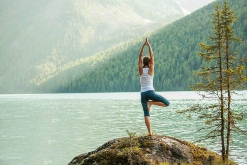 A woman reaping the emotional benefits of yoga by the lake.