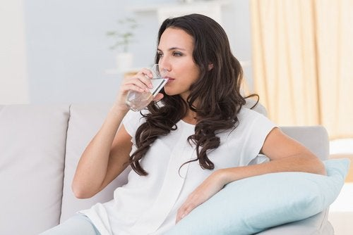 woman drinking water to help with bleeding hemorrhoids