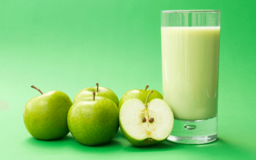 A glass of milk and some apples