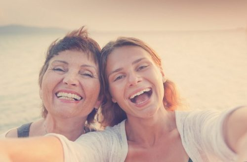 A mother and a daughter smiling.