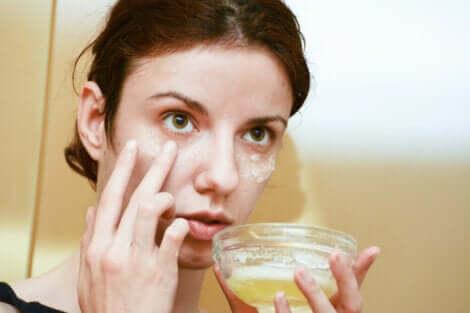 A woman applying a honey egg mask.