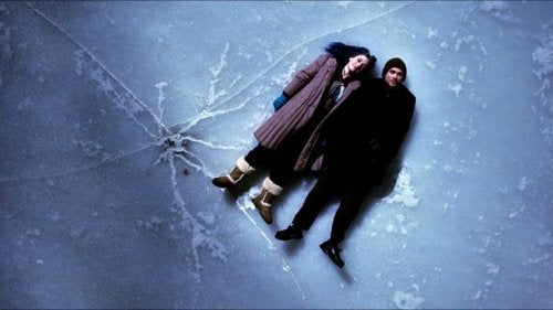 a couple laying on their backs on the ice