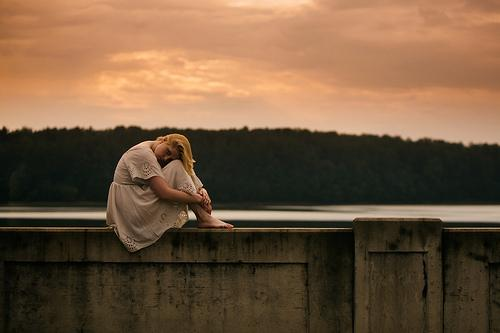 A silent girl sitting on a wall in nature