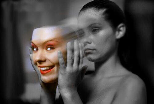 A woman taking off a mask that represents fake emotions and showing her true face