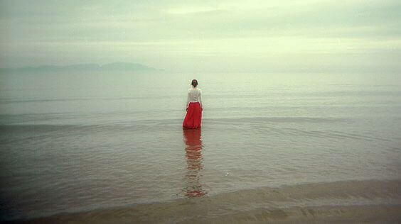 Woman in a red skirt standing by the ocean