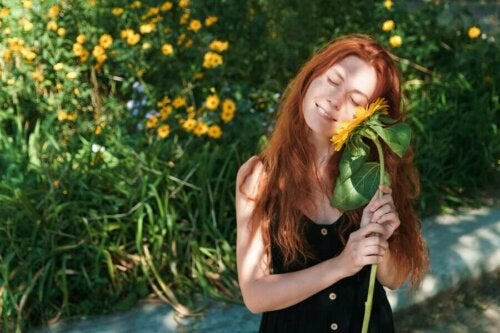A woman holding a sunflower.