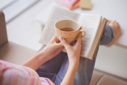 A person reading a book and drinking tea.