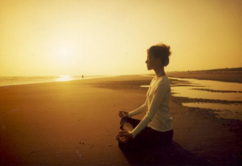 Woman meditating in a beach