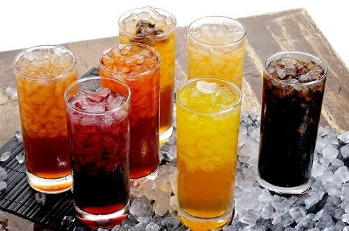 Sugary soft drinks of various colors in glasses.